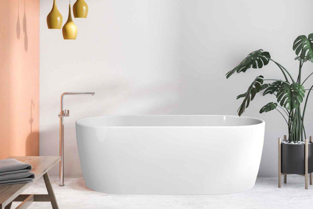 Embla helstøpt badekar fra Interform i hvit akryl. Gulvarmatur i krom. Betong gulv med marmor look og gule pendel lamper. Aprikosfarget vegg