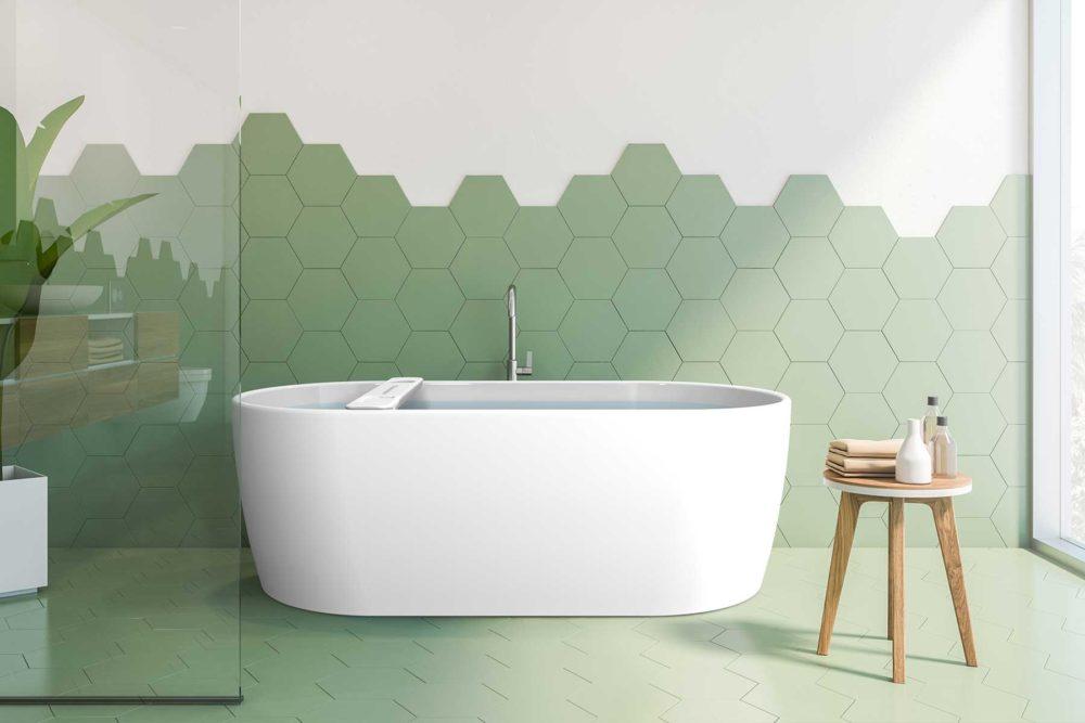 Embla helstøpt badekar fra Interform med badekarbro i hvit akryl. Grønne fliser på gulv og vegg.