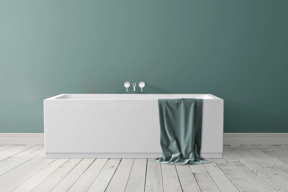 Idun badekar fra Interform. Nydelig grønn farge på vegg og rustikk gulv. Håndkle over badekarkant og armatur i krom.