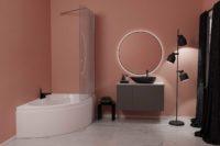 """Loke hjørnekar fra Interform. """"Himmelkyss"""" farge på vegg (fersken), svarte detaljer i armaturer, krakk, lampe og gardiner. Marmor gulv og grå møbel. Rundt speil med lys."""