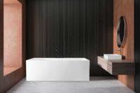 Mime helstøpt badekar fra Interform med Vega svart armatur. Mørke spiler / spilevegg. Terracotta vegg, hvit vask og rundt speil.