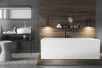 Mime er et elegant helstøpt badekar i akryl med god plass til karkantarmatur fra Interform. Her med Vega svart karkantarmatur. Tregulv og grå flisvegg. stilig og moderne interiør med pendel lamper