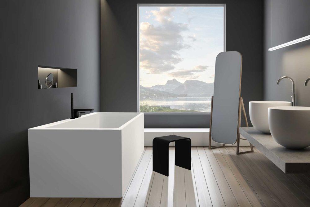 Mime er et elegant helstøpt badekar i akryl med god plass til karkantarmatur fra Interform. Her med Vega svart karkantarmatur og svart matt krakk. Tregulv og dus grå vegg. Nydelig utsikt mot fjorden.