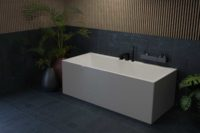 Mime 160 helstøpt badekar. Mørke flis på gulv og vegg samt spiler på vegg. Store vaser til grønne planter. Fin utsikt ut mot hage