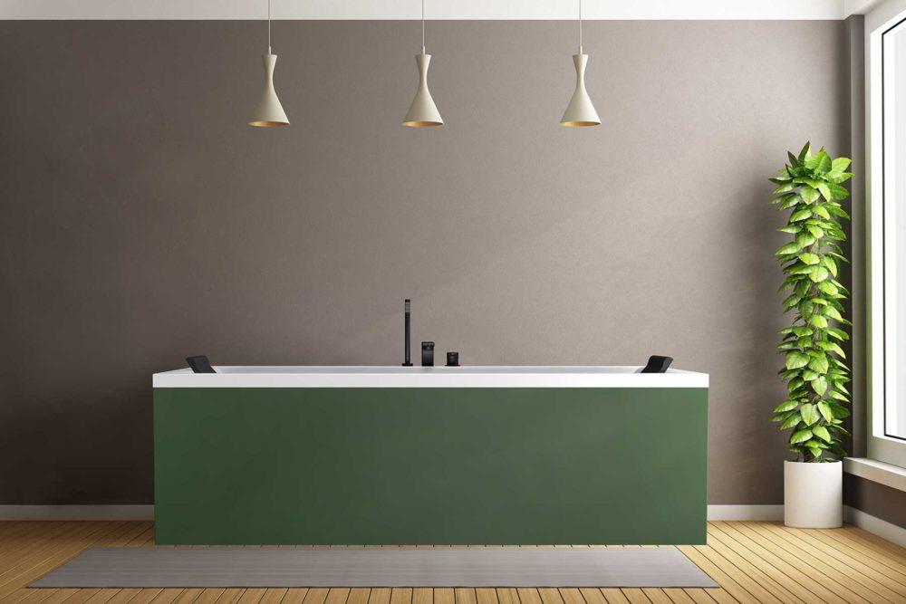 Nemo 190 badekar med farget panel, Vega svart armatur og svarte nakkeputer fra Interform. Dus grå vegg og tregulv. Pendel lamper i tak. Stor grønn plante ved vindu med utsikt mot hagen.