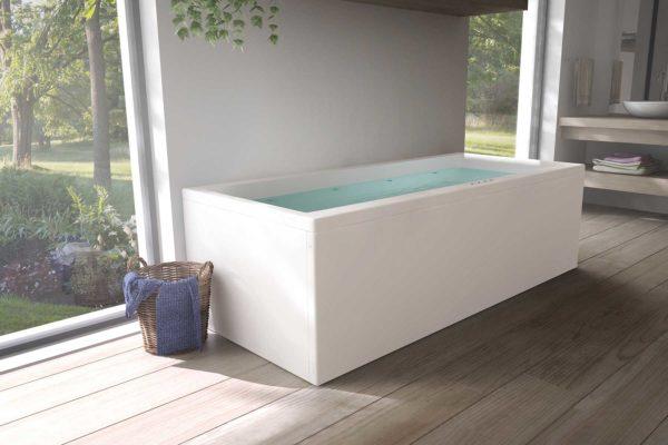 Nemo 180 badekar med massasjesystem / boblebad fra Interform. Tregulv og lyse vegger, servant i hvit porselen og krom armatur. Nydelig utsikt ut mot frodig hage.