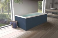 Nemo 180 badekar med massasjesystem / boblebad og farget panel fra Interform. Tregulv og lyse vegger, servant i hvit porselen og krom armatur. Nydelig utsikt ut mot frodig hage.