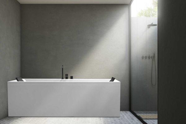 Nemo 180 badekar med Vega svart armatur og svarte nakkeputer fra Interform. Hexagonflis på gulv og vegg i betong. Svarte detaljer i dusj. Naturlig lysinnslipp i tak.