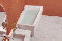 Nemo 160 asymmetrisk badekar i blank akryl. krom armaturer og hvit servant på hvit møbel. Terrakotta vegg og marmorgulv