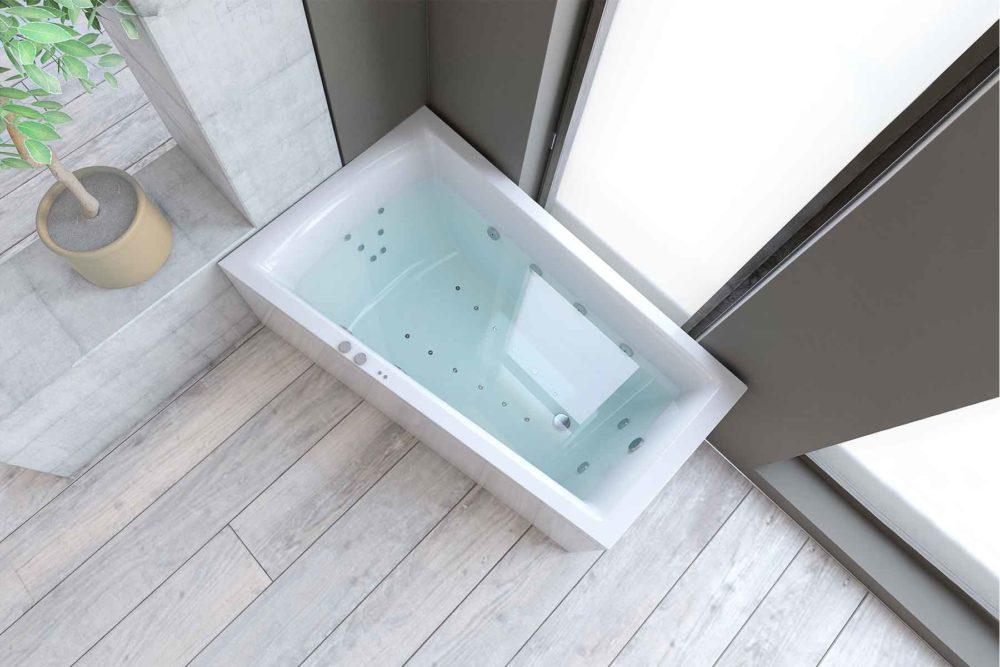 Nemo 160 badekar i venstre utførelse fra Interform. flis i treimitasjon på gulv. Betong og gråmalt vegg. Massasjebad / Boblebad med utsikt