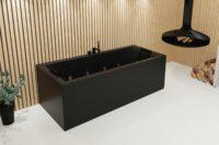 Nemo 190 badekar i svart matt. Svarte veggspotter og takhengende peis inkranset i spilevegger. Svart servant.
