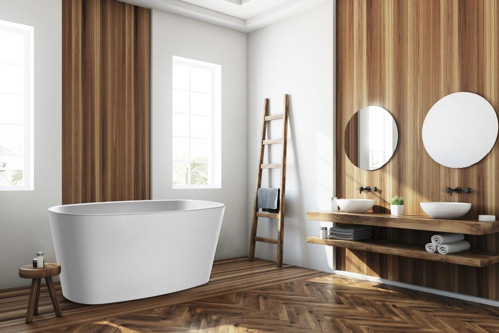 Urban frittstående kompositt badekar i hvit matt utførelse fra Interform. Tredetaljer i vegg og gulv. Runde speil og dobbel vask med svart armatur. Utsikt mot hage.