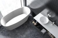 Urban frittstående kompositt badekar i hvit matt utførelse fra Interform sett ovenfra. Mørkt gulv og vegg med flis. flott utsikt fra badekaret. Hvit servant med hvit armatur.