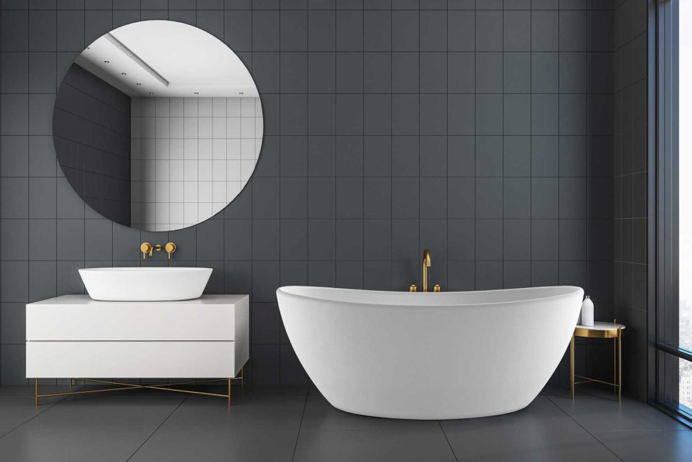 Viena badekar fra Interform i hvit matt kompositt / solid surface. gull armatur. mørke fliser på baderom. Rundt speil. Servant på hvit interiør
