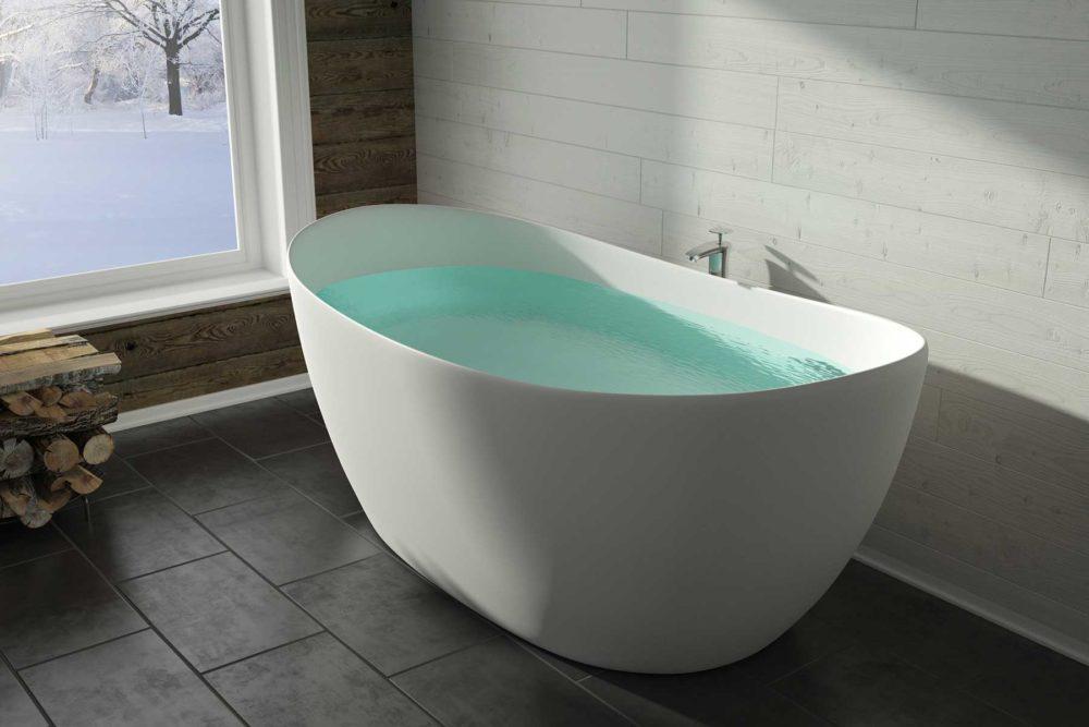 Viena badekar fra Interform i hvit matt kompositt / solid surface. Gulvarmatur på mørkt fliselagt gulv. Hvit trevegg og vindu med utsikt ut mot vinterlandskap.