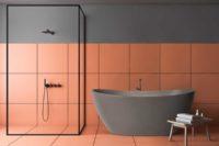 "Viena ""betong look"" badekar fra Interform i grå matt kompositt / solid surface. Terracotta farge på flis. Svart dusjvegg og svart armatur."