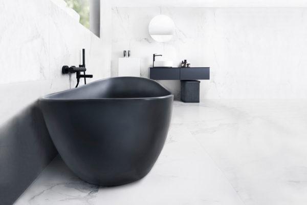 Viena Svart er et lekkert frittstående badekar. Svart vegg armatur. Det ovale designet skaper et mykt og moderne uttrykk. Utførelsen i svart matt kompositt gjør dette til et blikkfang. Marmor gulv og vegg. utsikt fra badekar. Svart innredning