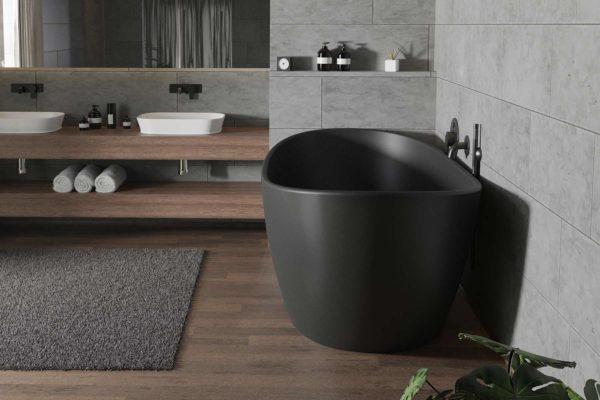 Viena badekar i svart matt kompositt fra Interform. Flis i treeimitasjon på gulv og betong på vegg. Dobbelvask med svart matt armatur. Nisje i betong og dør ut til hage.