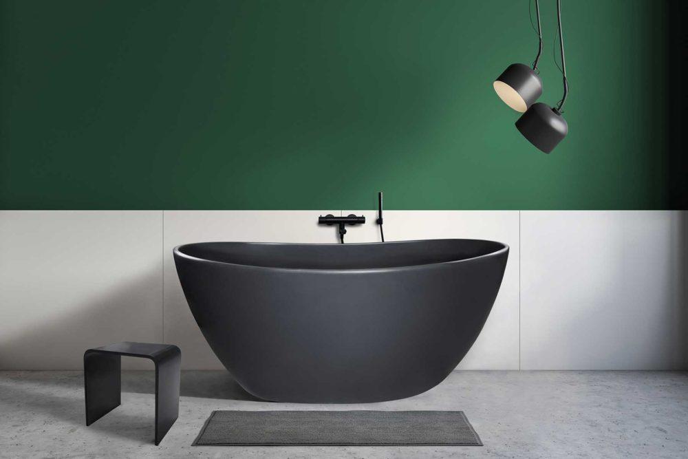 Viena Svart er et lekkert frittstående badekar. Svart vegg armatur. Det ovale designet skaper et mykt og moderne uttrykk. Utførelsen i svart matt kompositt gjør dette til et blikkfang. Svart veggarmatur på store hvite fliser og grønn vagg. Svart krakk og lamper