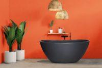 Viena Svart er et lekkert frittstående badekar. Svart vegg armatur. Det ovale designet skaper et mykt og moderne uttrykk. Utførelsen i svart matt kompositt gjør dette til et blikkfang. Store grønne planter på betonggulv og en aprikosfarget vegg