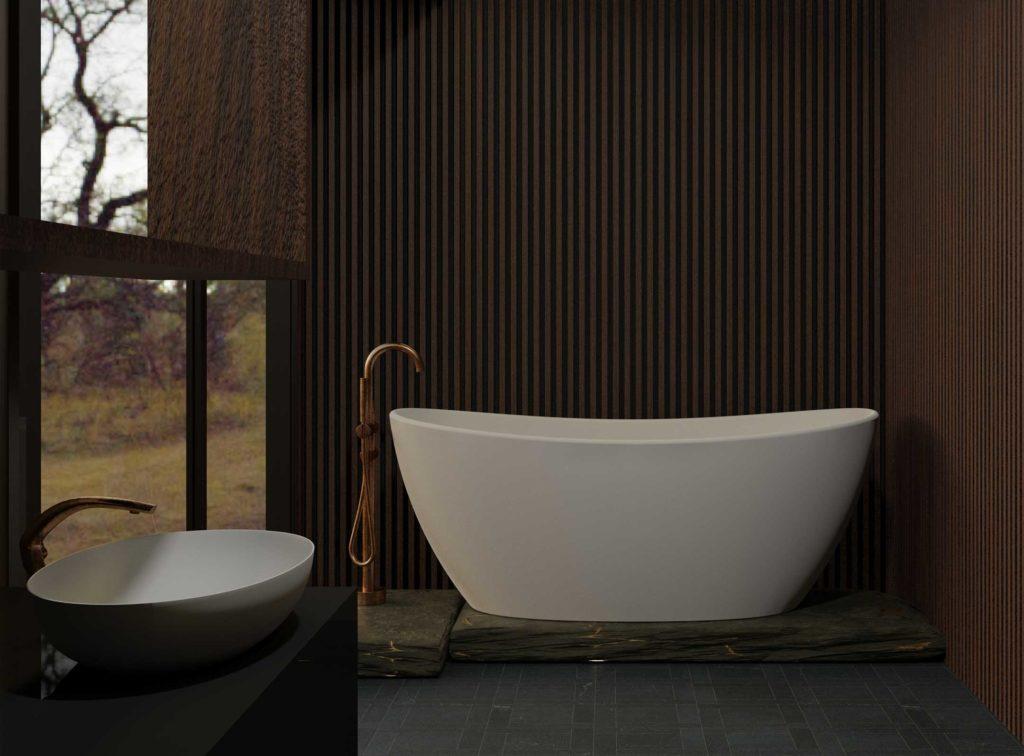 Viena badekar i hvit matt utførelse med gulvarmatur i børstet kobber. Mørkt flisgulv hvor selve badekaret står på steinhylle. Nydelig mørk spilevegg og stort vindu ut mot hage. Servant i hvit matt